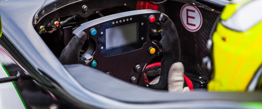 A driver holds the steering wheel of his supercar