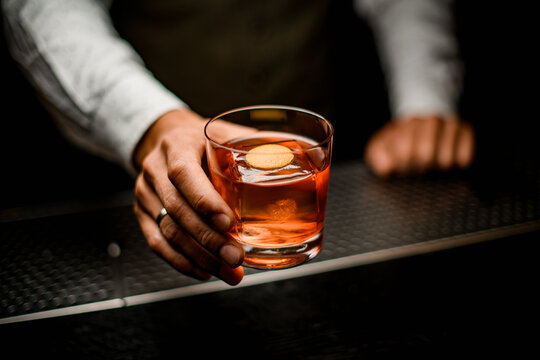 male bartender holds in his hand old-fashioned glass with cold alcoholic cocktail