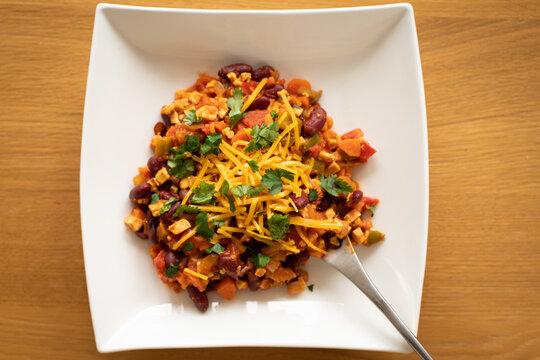 assiette de chili sin carne, plat sans viande, végétarien, sain recouvert de cheddar appétissant