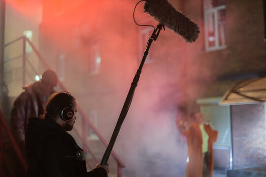 Sound engineer with a microphone on the set. A professional sound engineer at work on the filming of a movie
