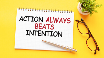 Word text action always beats intention on white paper card, business concept