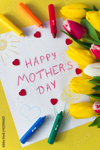 """Greeting card for Mom drawn by kid on Mother Day with the inscription """"Happy mother's day"""", bouquet of flowers colorful tulips, crayon pencils and red hearts on yellow background."""