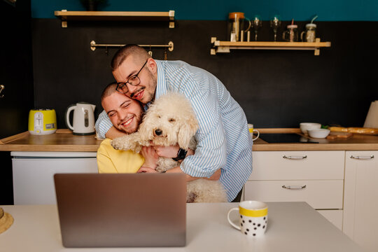 Happy community at home. Gay couple with dog during working hours