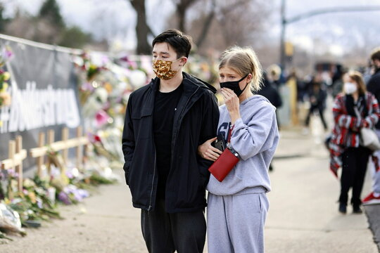 People grieve at the site of a shooting at King Soopers grocery store in Boulder