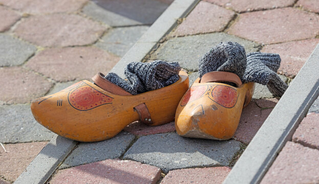 Old yellow wooden shoes with old socks at the side of a frozen river - Owner is ice skating