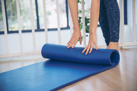 Woman hands rolled up yoga mat on gym floor in yoga fitness training room. Home workout woman close up hands rolling foam yoga gym mat. Woman barefoot home workout sportive healthy lifestyle concept