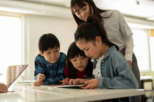 ICT in Education - Elementary School Students and Teacher Looking at Tablet PC