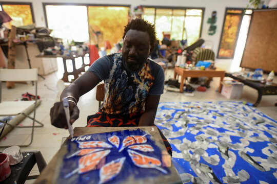 Senegalese artist Omar Ba signs his name on a painting of orange leaves in his studio in Bambilor,