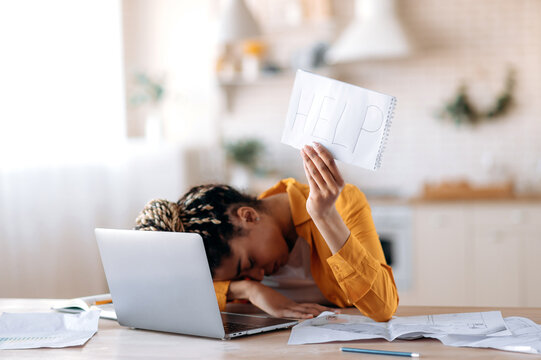 A frustrated African American female student is tired of studying at home, lies at her desk and holds a leaflet with the inscription help. Freelancer young woman need a rest from remotely work