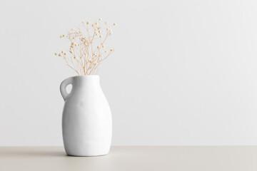 Obraz Dried gypsophila in a vase on a beige table. Flat lay with blank copy space. - fototapety do salonu