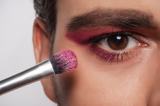 Men's makeup look. Close-up portrait of a young bearded man with a makeup brush