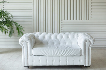 Fototapeta Classic luxury white leather chester sofa in white interior. Wood planks cover the wall obraz