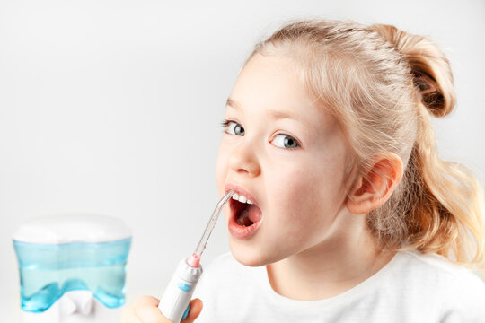Oral irrigator. Child girl brushes her teeth. Prevention of caries.