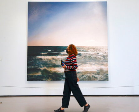 """A woman walks past the painting """"Seestueck"""" by German painter Gerhard Richter at the Kunsthaus Zurich art museum in Zurich"""