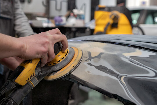 Crop anonymous male mechanic using machine for polishing car while preparing automobile for painting in workshop