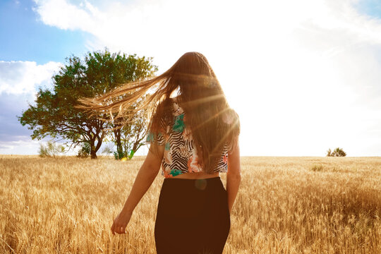 Back view of female standing on sandy road in field in spring and enjoying nature while looking away