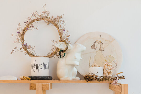 Wreath with dry plants near bunny statuette and hand painted chopping board near cup and decorative objects on wooden shelf near white wall