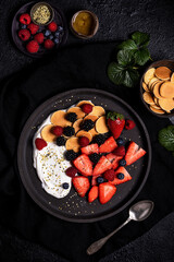 Top view of yummy healthy homemade breakfast with fresh assorted berries served with yogurt and cookies in black plate on table with ingredients
