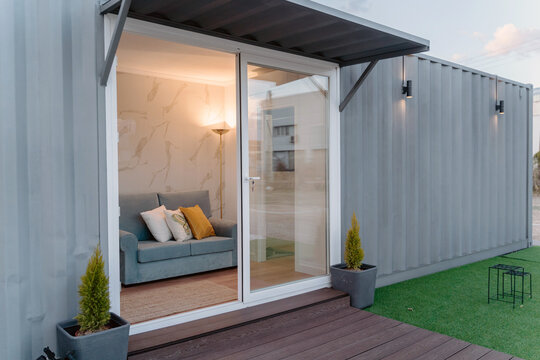 Contemporary gray container house with comfy sofa behind glass door located on grassy yard
