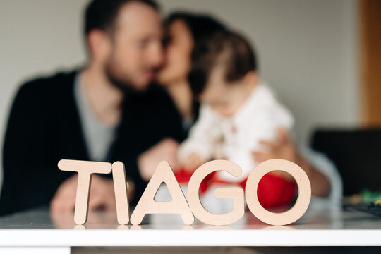 Wooden Tiago letter name placed on table near unrecognizable young parent kissing and embracing little child