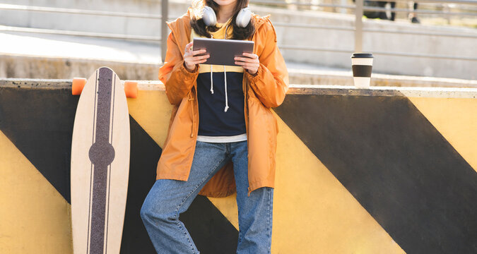 Crop anonymous stylish female browsing internet on tablet near longboard in town on sunny day