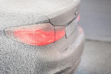 Obraz Cleaning car with white snow foam shampoo. Spraying white snow foam on a car. Spraying car shampoo foam to car. - fototapety do salonu