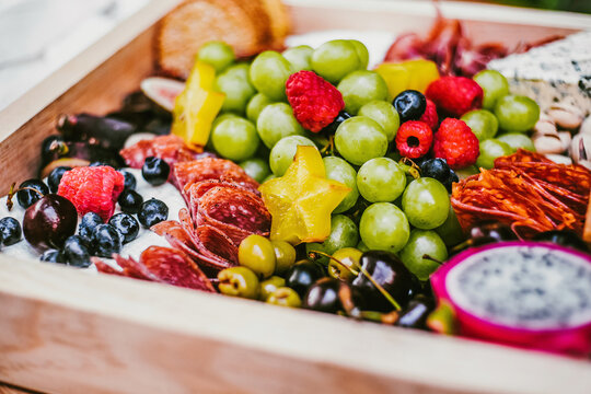 Meat delicacies near heap with fruits and berries in lumber box on table