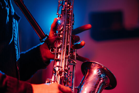 Crop faceless professional musician playing saxophone with fingers on keys during live concert in neon lights
