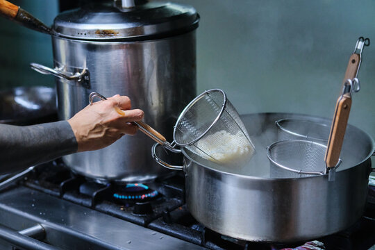 Stock photo of unrecognized chef cooking noodles in the kitchen of japanese restaurant.