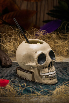 Ceramic polynesian tiki cup skull shaped with straw placed amidst dry grass with wooden fence and colorful feathers on blurred background