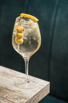 From above of crystal wineglass with Martini cocktail served with lemon zest and olives edge of wooden table