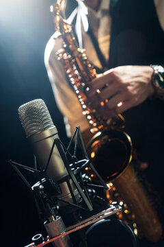 Crop unrecognizable male musician in classy outfit standing near microphone and playing alto saxophone during jazz concert