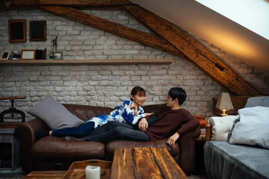 Lovely japanese couple chilling on sofa at home