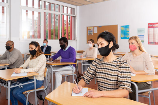 Portrait of asian woman in protective face mask during lesson in school for adults. Concept of necessary precautions and social distancing in coronavirus pandemic
