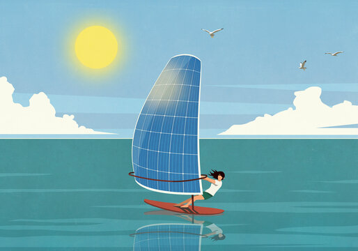 Woman windsurfing with solar panel sail on sunny ocean