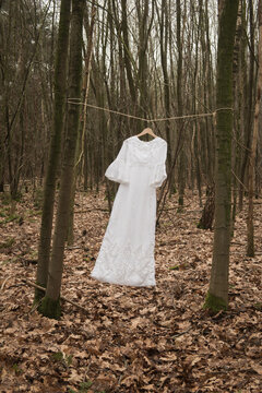 conceptual fine art photo of a white beautiful long bridal  wedding dress hanging on a cloth line in the wind in the forest