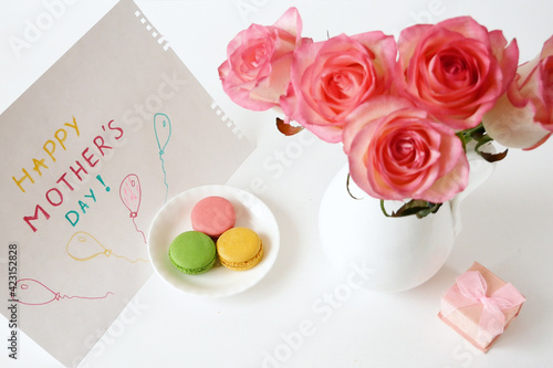 happy mother's day with beautiful bouquet of pink roses, eggs, french macaroni and card on green background, spring flowers flat lay