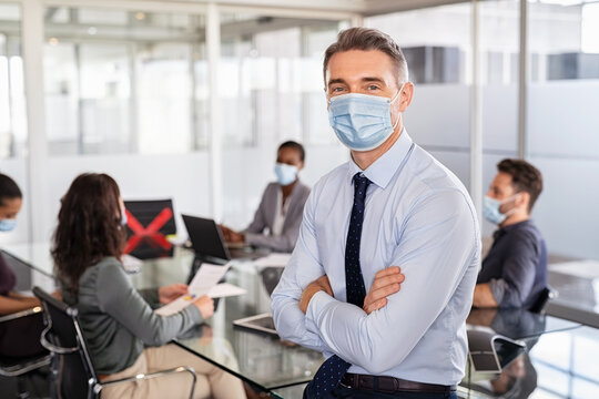 Happy businessman with face mask during covid