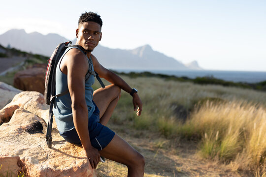 African american man exercising outdoors sitting on rock in countryside on a mountain