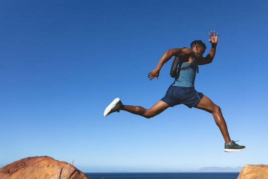African american man exercising outdoors jumping in countryside on a mountain