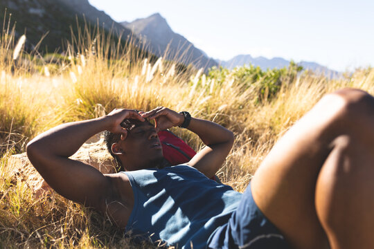 African american man exercising outdoors taking rest in countryside on a mountain