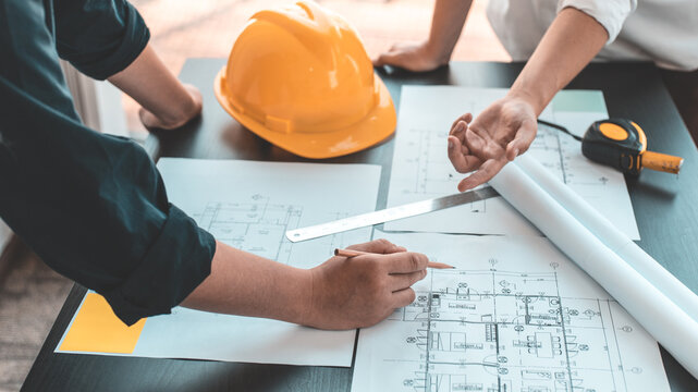 Meeting of engineers and architects in building planning, Consulting and brainstorming experts in architectural planning using blueprints, tape measure, rulers, laptop in designing buildings.
