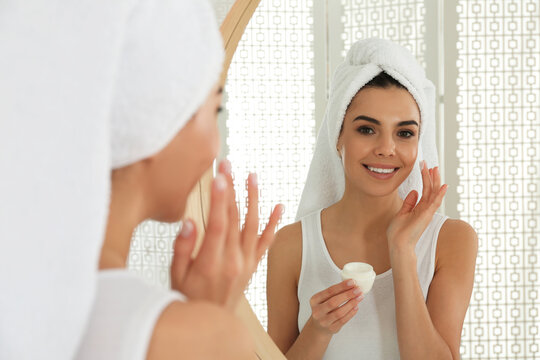 Happy young woman applying cream onto face near mirror in bathroom