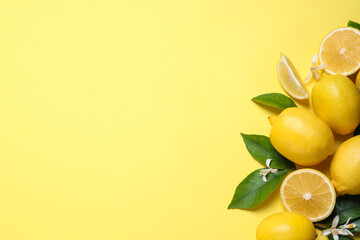 Many fresh ripe lemons with green leaves and flowers on yellow background, flat lay. Space for text