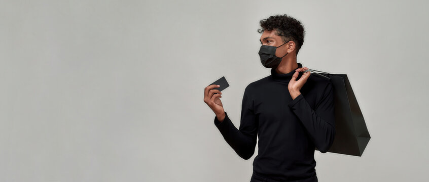Young guy in protective mask holding plastic card