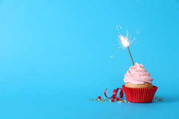 Birthday cupcake with burning sparkler on light blue background. Space for text