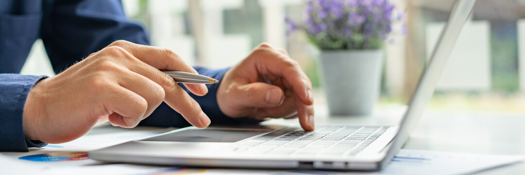A male accountant or a business man uses a laptop to calculate investment results. And making financial reports on the desk Business finance accounting concept