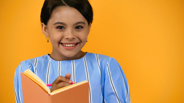 cheerful kid holding pencil and notebook isolated on yellow