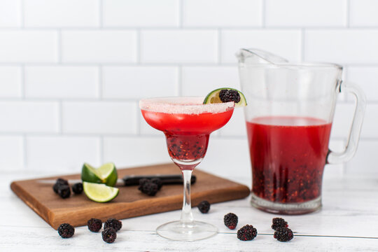 A blackberry berry margarita with fresh blackberries and limes in a margarita glass.