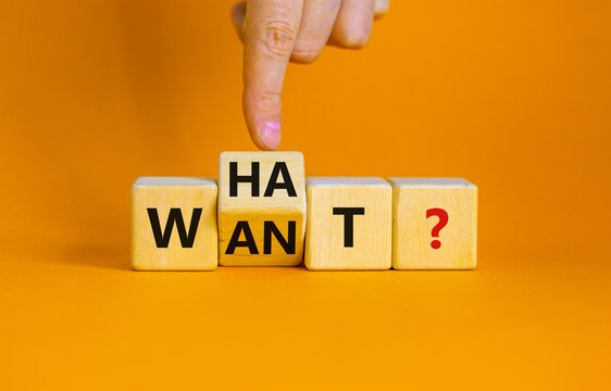 What do you want symbol. Businessman turns cubes and changes the word 'want' to 'what'. Beautiful orange background, copy space. Business, what do you want concept.